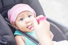 Fim acima da mão da mãe, uma colher do comida para bebê que alimenta seu bebê bonito pequeno para o jantar Olhar do bebê em sua m imagem de stock