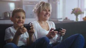 Fim acima da mamã entusiasmado e do filho apaixonados sobre o jogo vídeos de arquivo