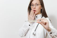 Fim acima da mulher chocada do doutor no vestido médico com estetoscópio, vidros Foco no termômetro clínico com febre alta fotografia de stock