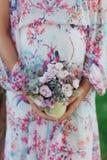 Fim acima da mulher gravida no vestido colorido perto da barriga nas mãos que guardam as flores imagem de stock