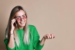 Fim acima da mulher loura nova que fala a alguém em seu telefone celular ao olhar na distância com expressão facial feliz foto de stock royalty free