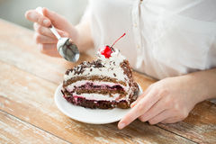 Fim acima da mulher que come o bolo da cereja do chocolate Imagem de Stock