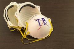 Fim acima da pilha branca da máscara e da palavra TB em crosss vermelhos no blackground Imagens de Stock