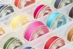 Fim acima das bobinas plásticas da máquina de costura com a linha colorida na caixa plástica imagem de stock