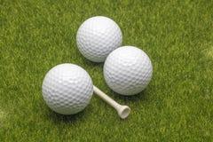 Fim acima das bolas de golfe e do T da vista no fundo da grama fotos de stock royalty free