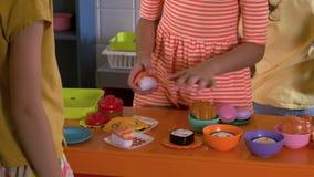 Fim acima das crianças que cozinham o sushi com cozinha do brinquedo vídeos de arquivo