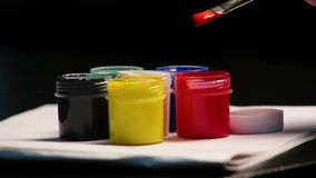 Fim acima das latas coloridos do guache com pincel sobre vídeos de arquivo