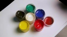 Fim acima das latas coloridos do guache com pincel sobre filme