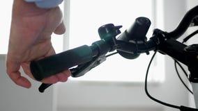 Fim acima das mãos do homem que testam freios e acessórios da bicicleta na sala da mostra video estoque