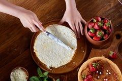 Fim acima das mãos do ` s da menina que adicionam o creme sobre o bolo delicioso da morango, fim acima, foco seletivo imagem de stock