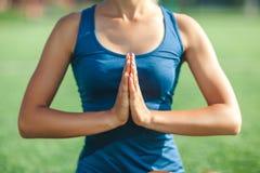 Fim acima das mãos na jovem mulher exterior da pose rezar e de ioga com olhos fechados em uma camisa azul imagem de stock