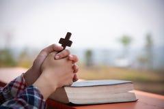 Fim acima das mãos novas que guardam a cruz de madeira sobre a Bíblia Sagrada e rezar Conceito cristão imagem de stock