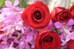 Fim acima das rosas vermelhas bonitas com a flor roxa da orquídea em um ramalhete da flor fotografia de stock royalty free