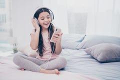 Fim acima de bonito bonito da foto ela seus earflaps espertos das mãos do telefone da menina para aprender o desgaste ondulado en foto de stock