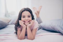 Fim acima de bonito doce bonito da foto sua menina cruzou os pés que encontram-se para baixo cabeça domingo doméstico da posse do imagem de stock