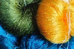 Fim acima de colorido de linhas de seda tailandesas cruas, do verde lustroso, do azul e do amarelo Foto de Stock