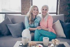 Fim acima de dois pessoas da foto ela sua tabela de chá quente da bebida da avó da criança da neta da mamã dos boatos das senhora imagem de stock royalty free