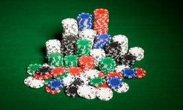 Fim acima de microplaquetas do casino na superfície da tabela verde Imagem de Stock Royalty Free