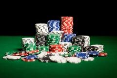 Fim acima de microplaquetas do casino na superfície da tabela verde Imagens de Stock