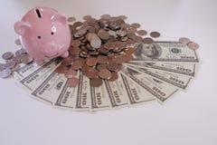 Fim acima de Piggybank com moedas e dinheiro sobre a mesa fotografia de stock