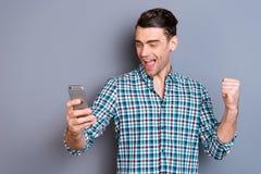Fim acima de surpreendente atrativo da foto ele ele seu telefone esperto do telefone novo das mãos de braços do homem excitado co fotografia de stock royalty free