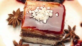 Fim acima de um bolo do caramelo com chocolate branco na placa branca filme