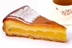Fim acima de uma fatia de bolo do limão com o copo do chá Foto de Stock Royalty Free
