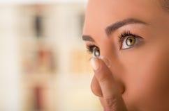 Fim acima de uma jovem mulher que coloca a lente de contato em seu fim do olho foto de stock royalty free