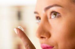 Fim acima de uma jovem mulher que coloca a lente de contato em seu fim do olho imagens de stock