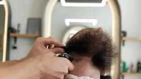 Fim acima do barbeiro que barbeia a barba no pescoço com o ajustador elétrico no barbeiro vídeos de arquivo