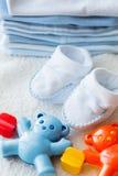 Fim acima do chocalho e dos sapatinhos de lã do bebê para recém-nascido Fotos de Stock Royalty Free