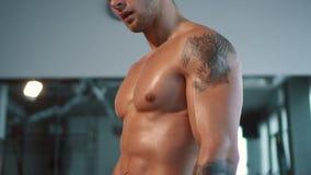 Fim acima do corpo de esporte masculino muscular no gym filme