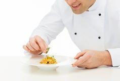 Fim acima do cozinheiro masculino feliz do cozinheiro chefe que decora o prato Imagens de Stock