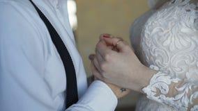 Fim acima do ` de espremedura e de acariciamento s do noivo e das mãos do ` s da noiva 4K vídeos de arquivo