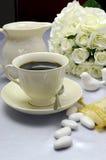Fim acima do detalhe no ajuste da mesa de jantar do café da manhã do casamento com o copo de café da porcelana e o jarro de leite  Fotografia de Stock
