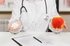 Fim acima do doutor fêmea colhido que senta-se na mesa, guardando a garrafa com os comprimidos brancos na palma, maçã vermelha no imagens de stock