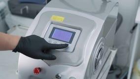 Fim acima do equipamento m?dico A mão fêmea gerencie sobre o dispositivo eletrónico para o procedimento cosmético, movimento lent vídeos de arquivo