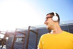 Fim acima do homem alegre que escuta a música com fones de ouvido imagens de stock royalty free