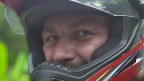 Fim acima do homem do motociclista da cara no capacete do moto que olha à câmera e ao sorriso Homem do motociclista do moto do re video estoque