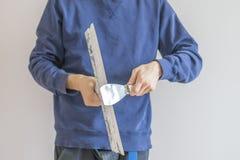 Fim acima do homem que guarda as facas de massa de vidraceiro que emplastram a casa f da parede, do funcionamento e do reparo foto de stock