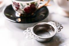 Fim acima do infuser de aço inoxidável do filtro do chá com o copo de chá da porcelana do borrão no fundo imagens de stock royalty free