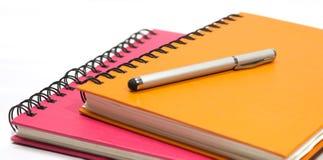 Fim-acima do livro e da pena alaranjados cor-de-rosa de nota Imagens de Stock