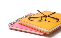 Fim-acima do livro e de olho-vidros alaranjados cor-de-rosa de nota Imagem de Stock