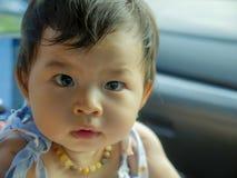 Fim acima do retrato isolado da cara do bebê chinês asiático doce e adorável que olha a câmera curiosa no estilo de vida infantil fotografia de stock