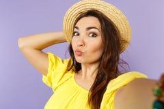 Fim acima do selfie disparado da jovem mulher engraçada no chapéu amarelo do verão do vestido que funde enviando o beijo do ar na imagens de stock royalty free
