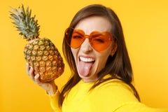 Fim acima do selfie disparado da jovem mulher louca nos vidros do coração que mostram a posse da língua o fruto maduro fresco do  foto de stock royalty free
