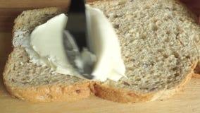 Fim acima do vídeo: manteiga cremosa de espalhamento em uma parte de pão vídeos de arquivo