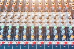 Fim acima do volume que ajusta botões no controlador audio do misturador na sala de comando foto de stock