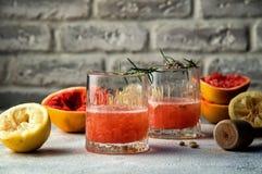 Fim acima Dois vidros de vidro enchidos com a bebida vermelha Em torno deles são as metades espremidas coloridos e o almofariz do imagens de stock
