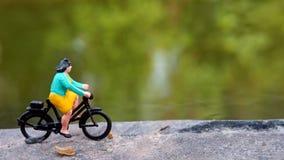 Fim acima dos brinquedos de Mini Figure Woman que bicycling na maneira do trajeto do lado do rio com espaço negativo ou da cópia  fotos de stock